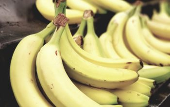 selective-focus-photo-of-bunch-of-bananas-on-black-surface-1093038